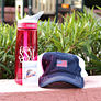 monogrammed pink camelbak with baseball hat in front of grass