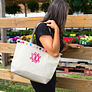 Girl wearing black shirt looking through fence with a Monogrammed Pom Pom Tote